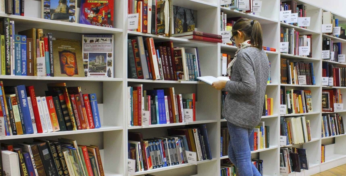 A girl selecting book from library book shelf to read