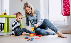 A toddler with Mom playing at toys