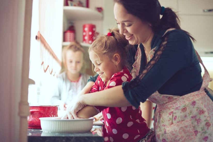 Good parenting; Mother teaching  daughter how to prepare meal